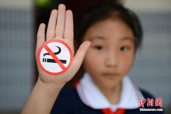 """资料图 为迎接第27个世界无烟日,苏州市东中市实验小学组织200多名学生,在学校广场上拼成了一个大大的""""禁止吸烟""""标志,并在手心上贴上""""禁止吸烟""""图标向老师、同学和家长宣传校园禁烟,为无烟校园吹响了号角。王思哲 摄"""