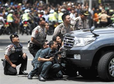 1月14日,印尼首都雅加达,警察持枪隐蔽在一辆汽车后。雅加达市中心当日发生多起爆炸,警方同武装分子交火,造成至少7人死20人伤。图/CFP