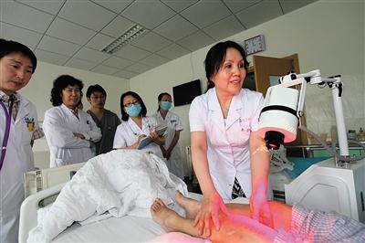为实施首都核心区医疗资源有序疏解,北京市卫生计生委在10个远郊区打造11个郊区区域医疗中心;并确定11家三甲医院对口支援。图为对口支援医院的专家和当地医生一起查房。