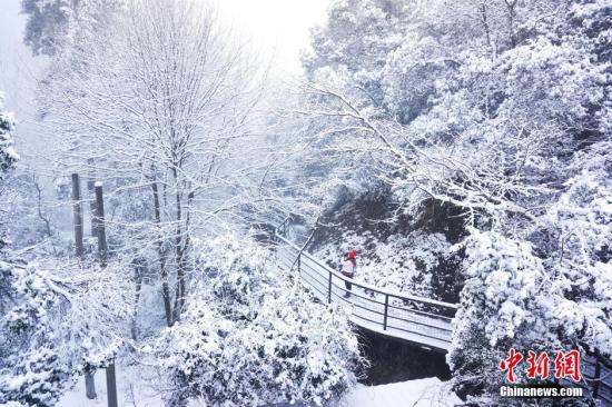 1月22日,浙江台州神仙居景区大雪纷飞,把景区覆盖成银装素裹的世界,在景区俯瞰,风雪冰天的山景朦朦胧胧、如梦似幻。中新社记者 周丽芳 摄