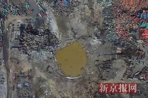 2015年8月26日,爆炸点的水坑经过处理呈黄色。新京报首席记者 陈杰 摄