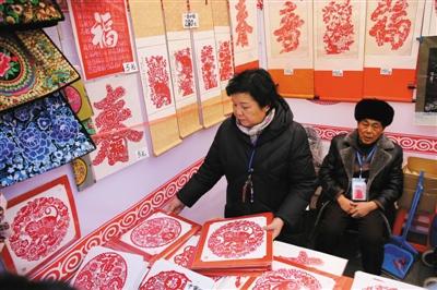 昨日,龙潭庙会上展出众多中华传统技艺,在剪纸展区内挂满了技艺传承人制作的剪纸。本版摄影/新京报记者 卢淑婵