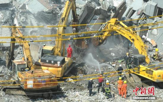 2月9日,在多人被埋的台南维冠金龙大楼,当局派出大型挖土机开挖。中新社记者 谭达明 摄