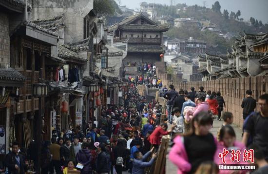 资料图:2月10日,正值大年初三,湖南凤凰古城迎来了春节假期的首个旅游高峰,数万游客涌入古城内欢度春节,景区到处是游人如织的火爆场面。 杨华峰 摄