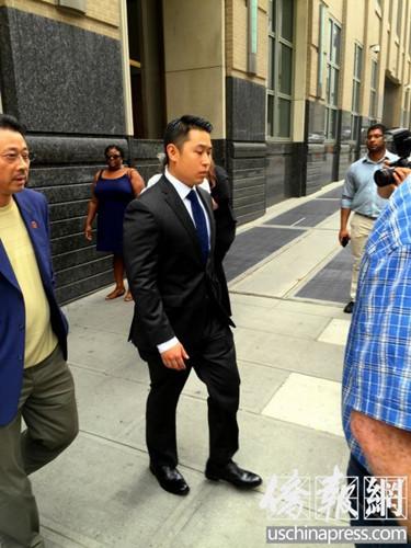 一身黑色西装的华裔警员梁彼得走出法庭。(美国《侨报》资料图/宋? 摄)