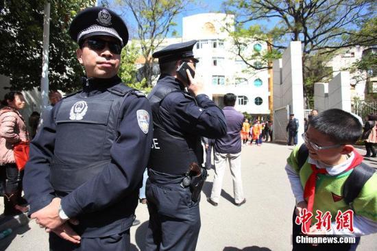 资料图:2014年3月3日,昆明,中午十二点,云师大附小的学生陆续放学走出小门,一位小同学好奇的打量民警身上的装备。图片来源:CFP视觉中国
