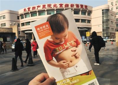 北京妇产医院门前,一名孕妇举着刚收到的脐血存储宣传单。