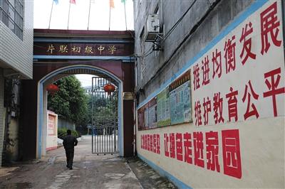 """片联中学墙上的标语。当地官员说,政府一直在做""""控辍保学""""工作,力图杜绝辍学和早婚。 A16-A17版摄影 新京报记者 薛�B"""