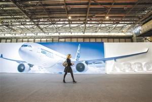 图为一位嘉宾从空客A330海报前走过。新华