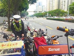 昨日,新洲路,一名协警整理查扣的电单车。深圳商报记者 肖兵峰 实习生 杨卫卫 摄