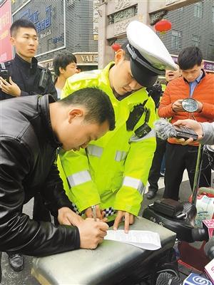 昨日,福华路,一名男子在查扣单上签字。深圳商报记者 肖兵峰 实习生 杨卫卫 摄