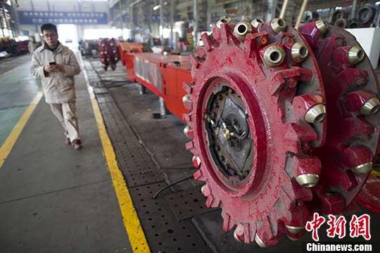 图为山西太重工人从采煤机前经过。(资料图片) 中新社记者 张云 摄