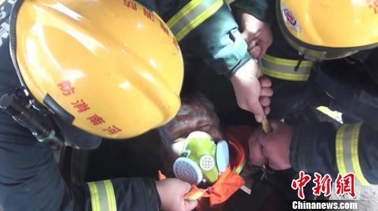 消防救援人员奋力将遇险被困工人从储油罐中拉出。 代军伟 摄