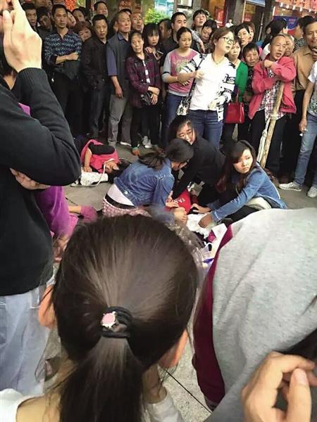 人和125路公交车站附近,4名女孩在对老太施救。