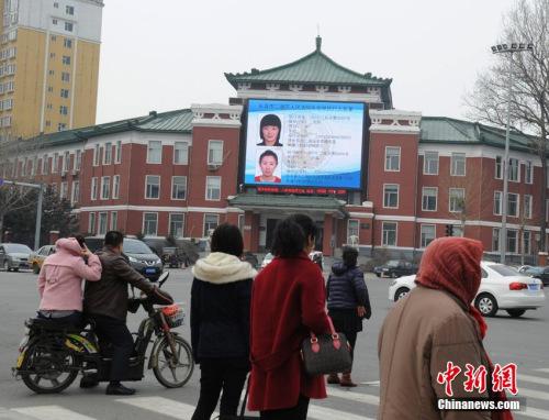 """资料图:2016年3月18日,长春市一繁华街路交会处,一块LED大屏幕滚动播放着24名""""老赖""""的特大照片,还包括他们的年龄、身份证号码、家庭住址,未履行的标的额等信息。"""