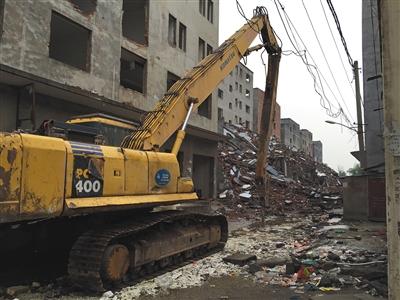 5月14日,一辆挖掘机在薛岗村拆迁工地,四周都是村民违建盖的楼房。