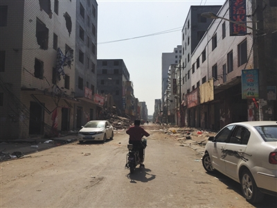 5月11日,郑州北郊薛岗村,一位村民骑车经过拆迁的街道。头一天,拆迁户范华培持刀杀死三人重伤一人后,被警方击毙。
