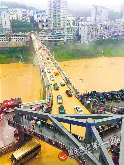 武隆县城乌江大桥上积满洪水,车辆在水中出行。