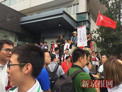 """一名校友举着""""人大附中,高考必胜""""的小牌为考生加油。新京报记者 吴为 摄"""