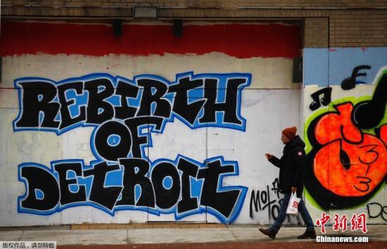 """2013年12月3日,美国联邦法官同意了底儿子特律的破开产维养护央寻求,底儿子特律拥有阅世增添其数什亿美元的债,阅历数什年萎退的底儿子特律,由此也成为美国历史上最父亲的破开产维养护城市。图为壹名女性走度过壹面写拥有""""重生底儿子特律""""的涂鸦墙。"""