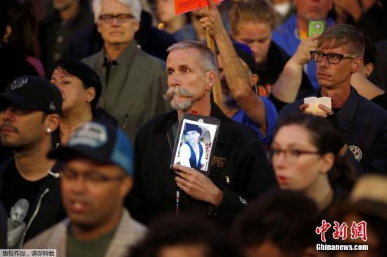 参加默哀活动的旧金山民众手持遇难者照片。多名国际政要也对枪击案表示谴责,并向美国民众表示哀悼。