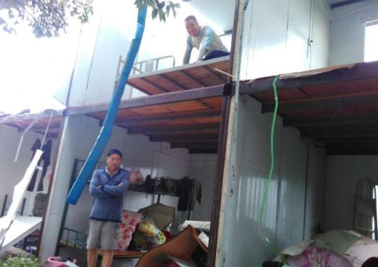西三环两侧,一个建筑工地的工人宿舍被大风摧毁,宿舍活动板房的墙壁被风刮飞。