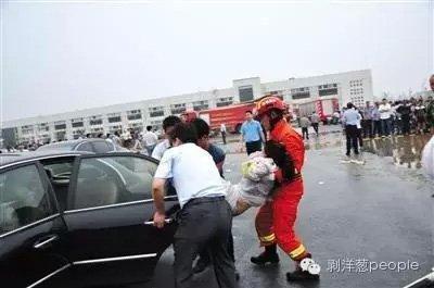 消防队员和民众一起把伤员抬上车。图片来自网络