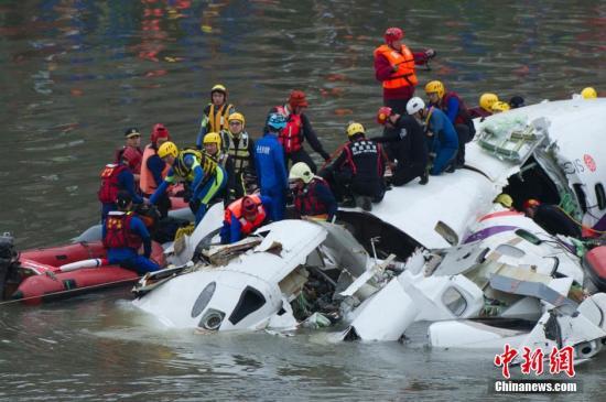 资料图:2015年2月4日上午,搭载58人的台湾复兴航空GE-235班机从台北松山机场起飞后不久坠入基隆河。图为当地救援人员在空难现场实施救援。中新社发 邵航 摄