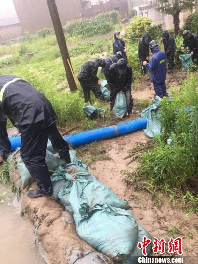 常州市公安局焦溪派出所组建30人的抢险队伍,在居民集中处外围强筑防水堤坝。 唐娟 摄
