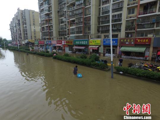 连日来持续强降雨,南京市七桥瓮一带大面积积水,附近门面房的业主在门面房门口堆了很多的沙袋排险。 郭亚楠 摄