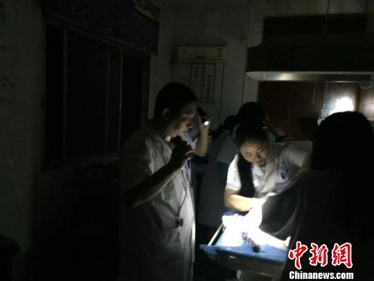 医生打着手电筒为新生儿接生 罗中华 摄