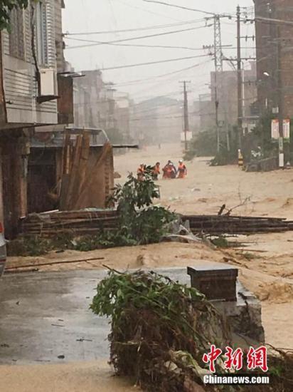 """7月9日13时45分,本年第1号飓风""""尼伯特""""在福建石狮内地登岸。受飓风作用,强降雨侵袭福州,多地内涝重大。图为福州闽侯县受灾重大。 中新社记者 陈帆 摄"""