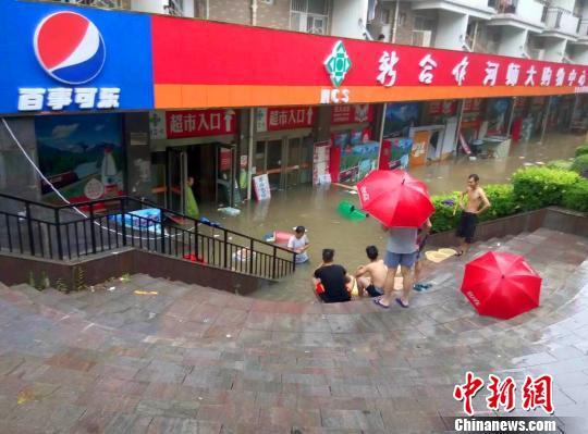 """图为河南师范大学校园内商铺被淹,学生、商家被""""困""""在台阶上。 周小云 摄"""