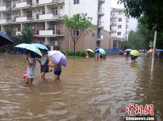 """图为河南师范大学校园内,学生卷起裤腿在水中穿行,该校校园内部分路段积水严重,操场变身""""泳池"""",校园商铺被淹。 周小云 摄"""