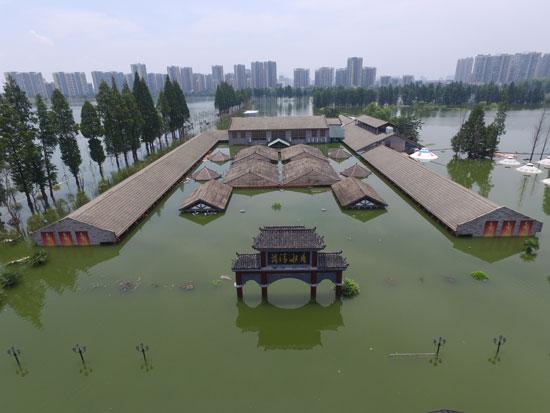 7月8日,武汉三环内野芷湖大桥边,一家之前曾被媒体曝光的填湖违建饭店被洪水淹得只露出了屋顶。牛牛/视觉中国