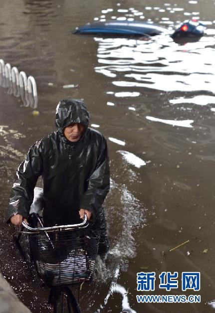 7月20日,市民在天津市河东区东风地道涉水前行,身后一辆汽车被水淹没。当日,天津市遭遇暴雨袭击,部分道路和涵洞出现严重积水。 新华社记者 岳月伟 摄