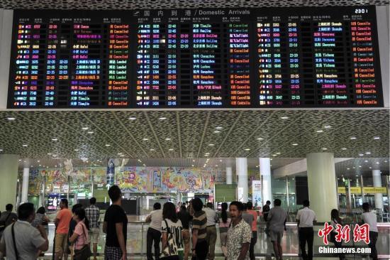 """8月1日,深圳机场,到达大厅的显示屏上滚动播放着被取消航班的信息。当日,受台风""""妮妲""""影响,深圳机场启动三防红色预警,各航空公司已在深圳机场取消8月1日至2日两天进出港航班140班。 中新社记者 陈骥�F 摄"""