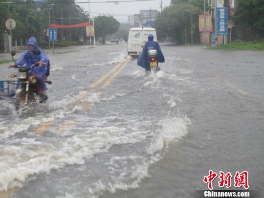 图为17日下战书,海南省临高县的县城,局部路段积水成河,车在水中行驶如行舟。 付美斌 摄