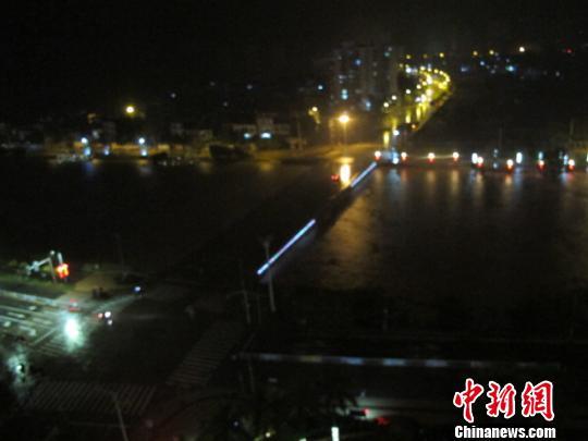 图为17昼夜晚,从海南省临高县穿城而过的文澜江的江水一直上涨,大水翻滚。 付美斌 摄