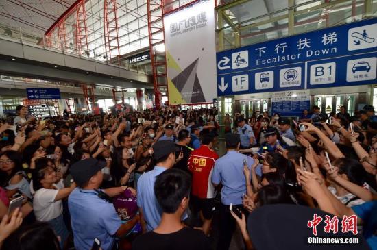 8月20日,包揽里约奥运4枚金牌的中国乒乓球队抵达首都机场,受到球迷的热情追捧。图为刘国梁、马龙、张继科、刘诗雯等出现在首都机场,被大批媒体和球迷包围。中新网记者 金硕 摄