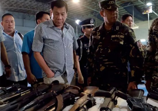 当地时间8月10日,菲律宾总统杜特尔特在军营检查禁毒中收缴的枪支。