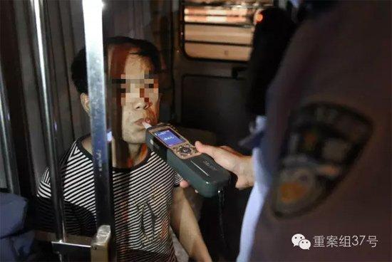 7月28日晚,朝阳区白家楼桥下,朝阳交通支队双桥大队的民警,正在对过往司机进行酒驾检测。并将确定酒驾者带进警车。 新京报记者 尹亚飞 摄