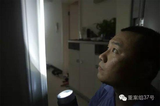 7月27日,丰台枫竹苑小区,办案民警检查防盗门被划痕迹。 新京报记者 彭子洋 摄