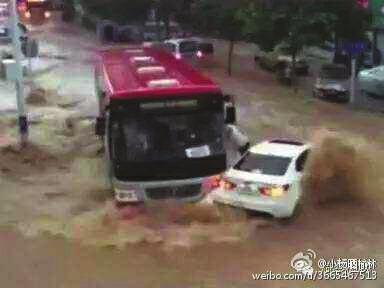 小轿车眼看要被洪水冲走 他驾驶公交车迎面顶住