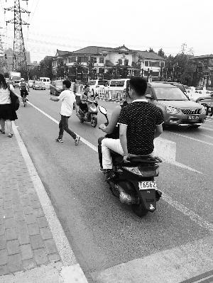 黑摩托载客逆行。