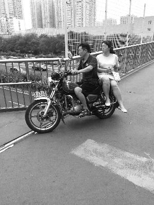 黑摩托搭载乘客直接开上过街天桥。