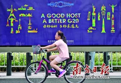 一个小朋友骑车从g20宣传画前经过