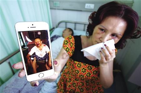 庞密斯展现丈夫被打时的相片,而她身上仍有显着的淤青。记者 李化 摄