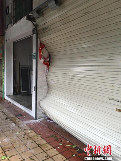 商店升降门被台风拉扯变形。 陈悦 摄
