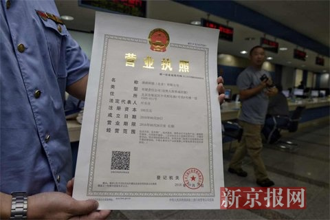 商人员展示新的营业执照。 新京报记者 王嘉宁摄